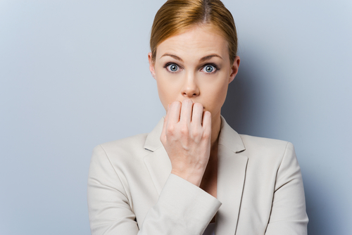 Nervous young woman biting her nails while standing against grey background