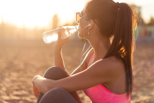 fitness athlete woman drinking water after work out exercising on sunset evening summer in beach outdoor portrait.