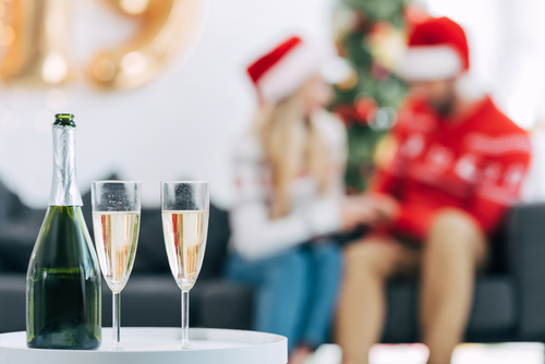woman and man celebrating the holidays, focused on champagne