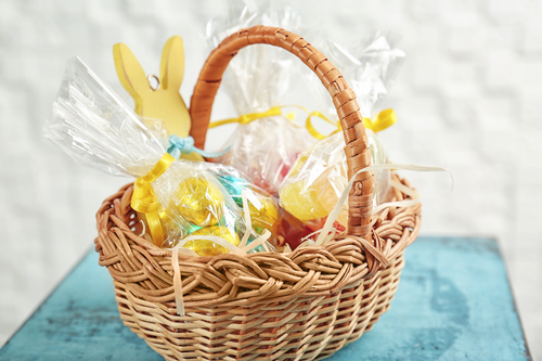 Easter basket with sweets and presents on wooden table