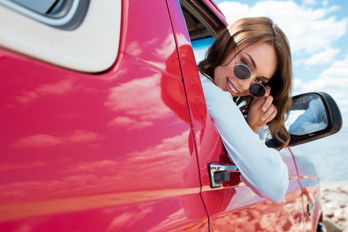 woman with sunglasses looking outside the car window
